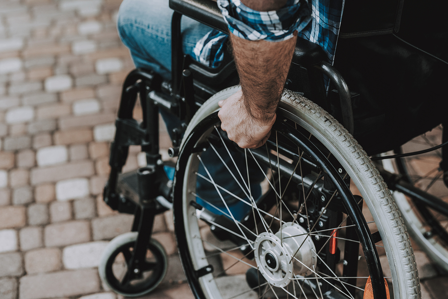 Disappointed man in wheelchair with arm on wheel after a claim denial.